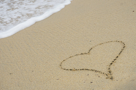 Heart shape drawn in sand on beach with sea wave