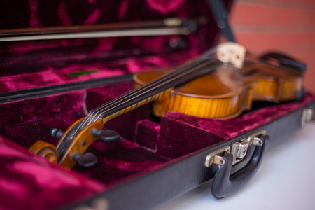Violin and bow in dark red case. Close up Stock Photo