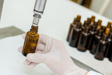 Close up of female lab worker hand with gloves filling the bottle with syrup.