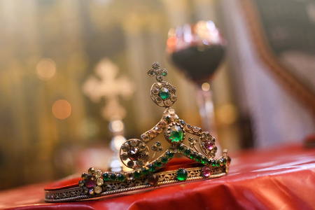 Isolated wedding crown and blurred glass of vine and cross in background. Orthodox church wedding accessories.