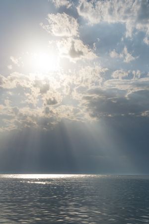 Sea water on cloudy day, nature background . The rays of the sun break through the clouds. Ocean view on cloudy summer day.