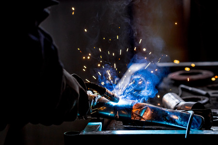 Male worker wearing protective gloves while repairing car exhaust pipe with welding machine