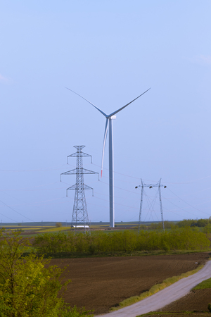 Windmill turbine on agricultural field with large electricity towers in front, blue sky in background. Banco de Imagens