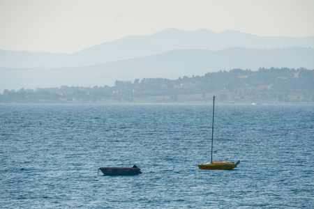 Small white motorized boat and yellow sailboat anchored on the sea.
