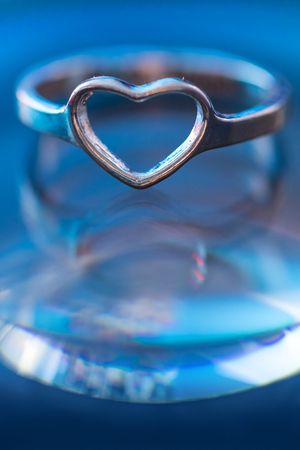 Silver heart shape ring with light blue background. Reklamní fotografie