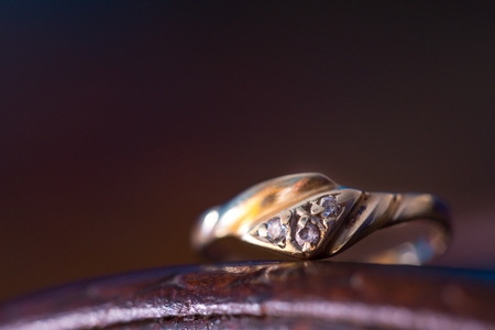 Gold ring with crystals on purple background.