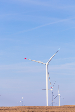 Windmill turbine farm with partly cloudy blue sky in background. Renewable energy wind turbines