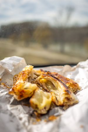 A piece of burek with cheese on white paper.