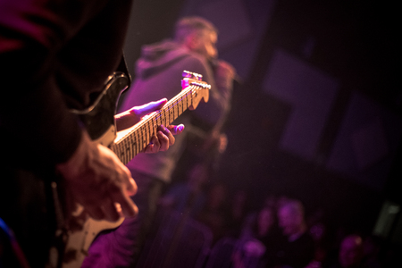 The guitarist plays an electric guitar on stage with lights in the background. Close up.