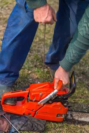 Old man in blue pants starting orange chainsaw.