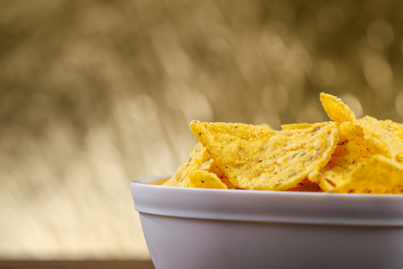 Yellow nacho in white bowl on the wooden table.