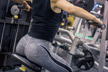 Young strong woman from behind training upper body at the gym. Beautiful booty shaped woman in gym.