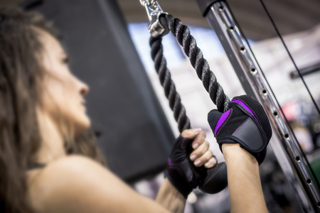 Close up of young woman hand wearing black and purple gloves in gym and holds black rope of exercise equipment.