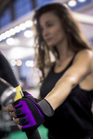 Close up of young woman hand wearing black and purple gloves in gym and holds black and yellow handrail of exercise equipment.