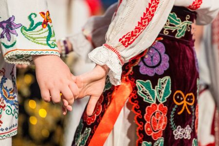 Close up of hands of young Romanian dancers perform a folk dance in traditional folkloric costume. Folklore of Romania