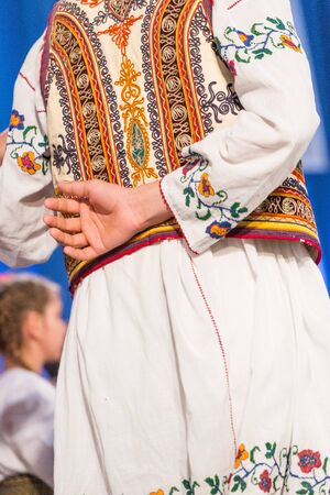 Young Romanian dancer hold hand on his back while perform a folk dance in traditional folkloric costume. Folklore of Romania