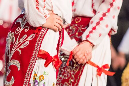 Close up on hands of young Romanian dancers perform a folk dance in traditional folkloric costume. Folklore of Romania