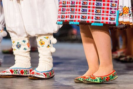 Close up of legs of young Romanian dancers perform a folk dance in traditional folkloric costume. Folklore of Romania Stock Photo