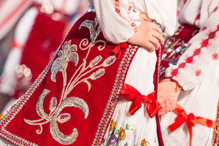 Close up s of young Romanian dancers perform a folk dance in traditional folkloric costume. Folklore of Romania