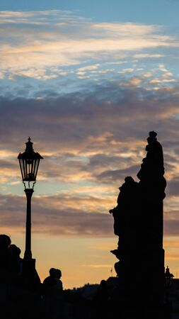 Silhouette of statue on Charles Bridge in Prague, at sunset with cloudy sky. Medieval Gothic bridge, finished in the 15th century, crossing the Vltava River