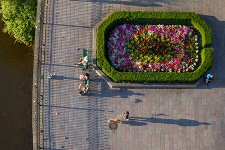 Top view of people sitting on green benches next to decorated flowers in Prague in front of Charles Bridge Museum 스톡 콘텐츠