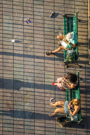 Top view of people sitting on green benches in Prague in front of Charles Bridge Museum