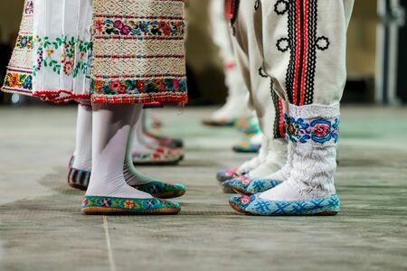 Cerca de calcetines de lana en las piernas de jóvenes bailarines y bailarines rumanos en traje folclórico tradicional. Folklore de Rumania Foto de archivo