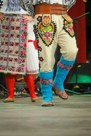 Close up of blue wool socks on legs of young Romanian dancer in traditional folkloric costume. Folklore of Romania