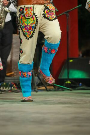 Close up of blue wool socks on legs of young Romanian dancer in traditional folkloric costume. Folklore of Romania 免版税图像