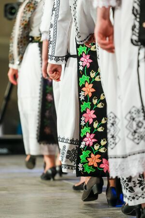 Close up on detail of young Romanian female dancer traditional folkloric costume. Folklore of Romania