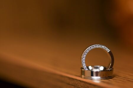 Close up of two wedding rings on flat wooden surface