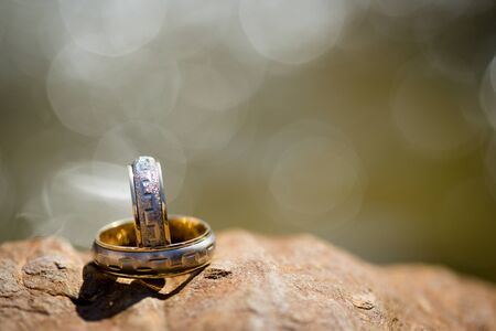 Close up of two wedding rings on rock