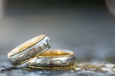 Close up of two wedding rings on concrete with blurred background