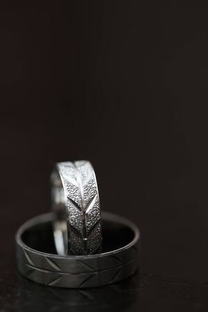 Two wedding rings on dark wooden surface with blurred background