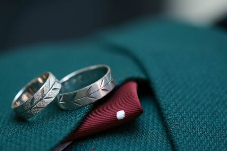 Two rings on green male wedding suit. Macro close up of wedding rings Stock fotó