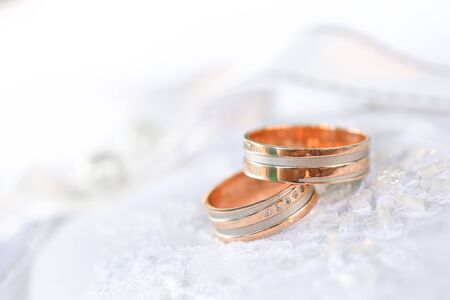 Dos anillos de boda de bronce sobre textil blanco Foto de archivo