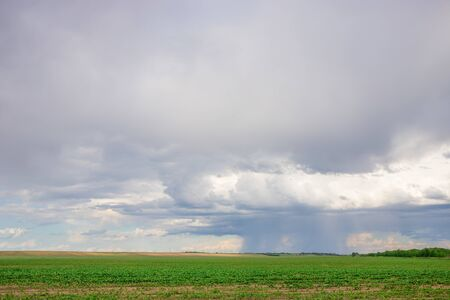 Dark clouds on sky with incoming rain over agricultural fields in distance Stock fotó