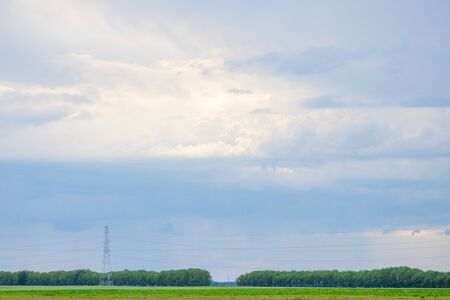Rainy clouds over trees and agricultural fields