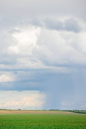 Dark clouds on sky with one part with rain over agricultural fields in distance