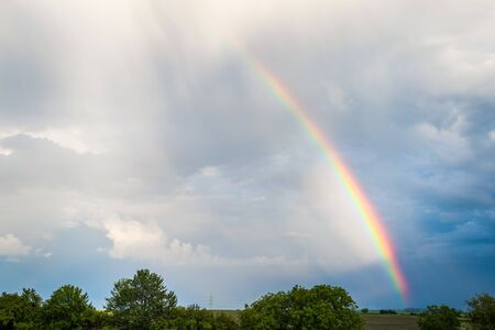 Rainbow over trees and agricultural fields with cloudy sky in background
