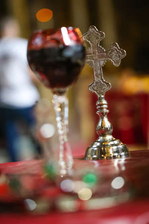 Gold cross next to wine for weddings in the orthodox church. Church wedding attributes.