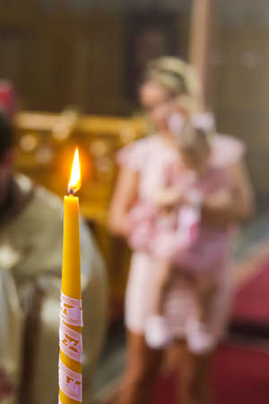 Burning candle at Orthodox christening with blurred background