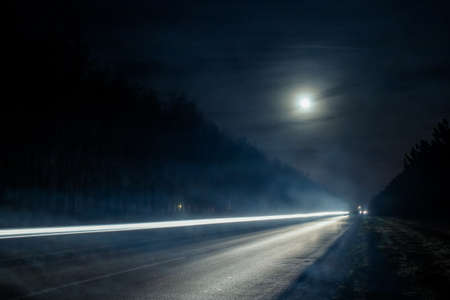 Light trails from vehicles traveling on rural road, surrounded by two rows of trees, late at night with moon on sky.