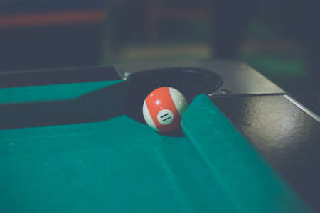 Red, number 11, billiard ball in a pool table. Vintage style noise effect