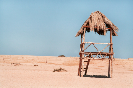 Lifeguard tower in Egypt. Wooden Lifeguard tower at the sandy beach with palm leaf roof top