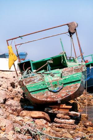 Old fishing boat. The old fishing boat stranded on the rocky coast in Egypt. Abandoned wooden fishing boat of colorful colors stranded on the beach for long time.