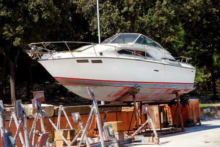 Jacht motorboot in de haven. Witte jachtmotorboot op de onderhoudsstructuur bij de haven. Houten jacht uit de zee voor onderhoud havenhaven. Yachting concept. Stockfoto