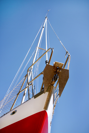 shipbuilding: Bow of red and white sailboat, close up, low angle.