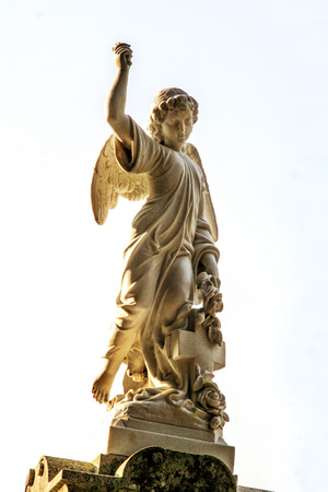 Stone statue Angels, with a stone cross and flowers