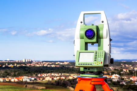 topografo: Fall time land surveying, total station set in the field Foto de archivo